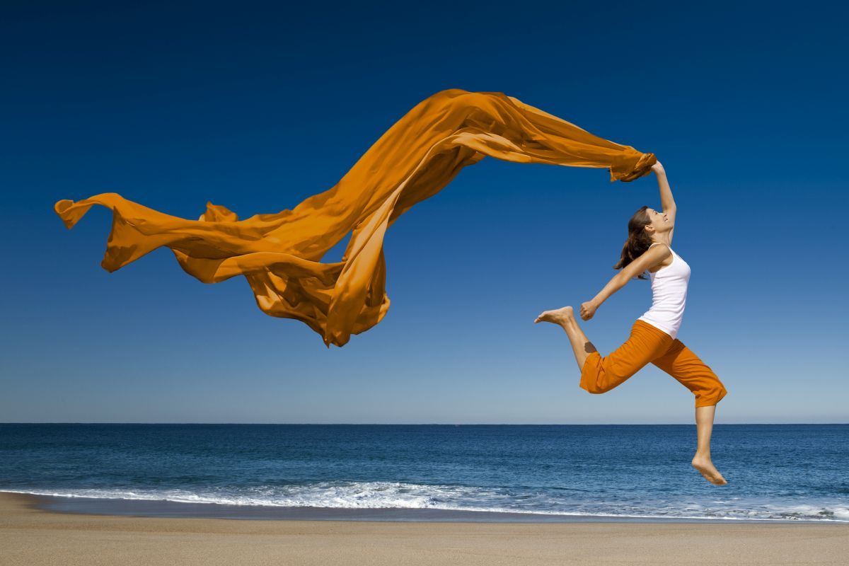 mujer corriendo y saltando en la playa cuidando su cuerpo